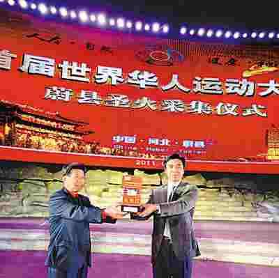 图首届世界华人运动大会主席聚博圣与燕旺林向观众展示采集后的火种灯。