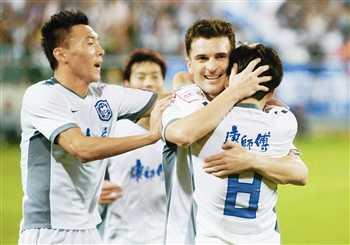 图为足协杯赛泰达队攻破陕西人和队大门后,队员们相拥庆祝。本报记者 宁 柯摄