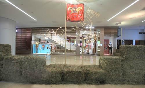 由马草、丝巾和金属线条勾勒的骏马雕塑组成爱马仕广州太古汇专卖店开幕现场