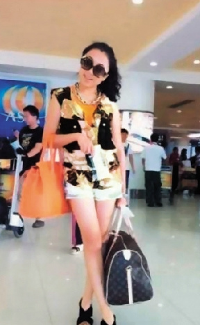 右手挎一个橘红色爱马仕包,左手提一个LV大旅行包。最近这张照片在网上疯传。