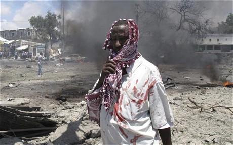 索马里首都摩加迪沙政府大楼发生爆炸,图为一名受伤的人站在爆炸现场。