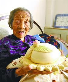 捧着大寿桃两位老寿星笑开花感叹年轻时也会做手艺还不错