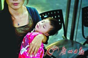 10月5日广州塔电梯急停后,一位母亲抱着孩子坐在售票大厅里,依然惊魂未定。