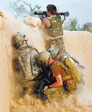 一名阿富汗士兵向疑似塔利班武装分子发射火箭弹,在他身后为美军士兵。