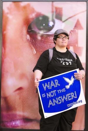 """10月7日,在华盛顿,示威者安杰拉举着写有标语""""战争不是答案""""的牌子。"""