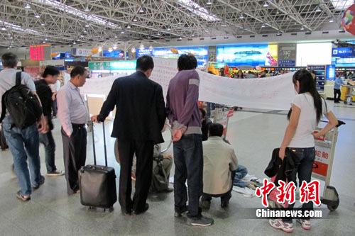 朱兰英等人拉起横幅抗议,引起众多过往旅客围观。 史广林 摄