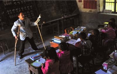 ①两根细拐杖,撑起患病躯,谭定才为学生读课文。