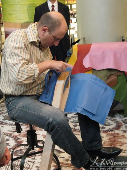 图为一位法国工人师傅正在演示红遍好莱坞的铂金包制作过程,每穿好一针,都会抬头跟大家讲解一下。(人民网 王千原雪摄)