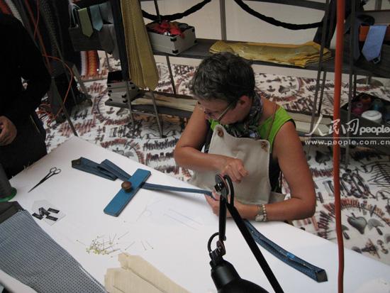 工人在向参观者演示领带的制作过程,整个过程并没有用到任何缝纫机器,都是工人手工制作的。(人民网 王千原雪摄)