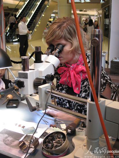 美丽的珠宝制作工人正在显微镜下精工细琢一副耳环。来自时尚之都的工人品味不凡。(人民网 王千原雪摄)