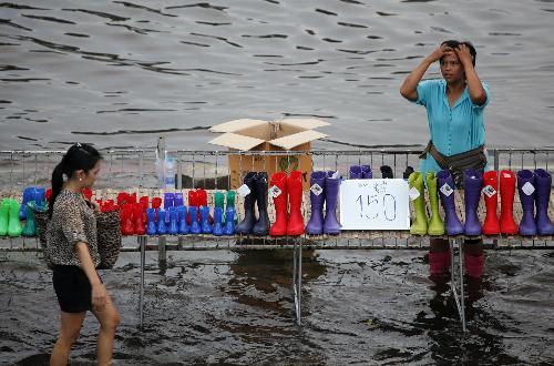 10月18日,泰国一名妇女在曼谷附近兰实地出售雨靴。