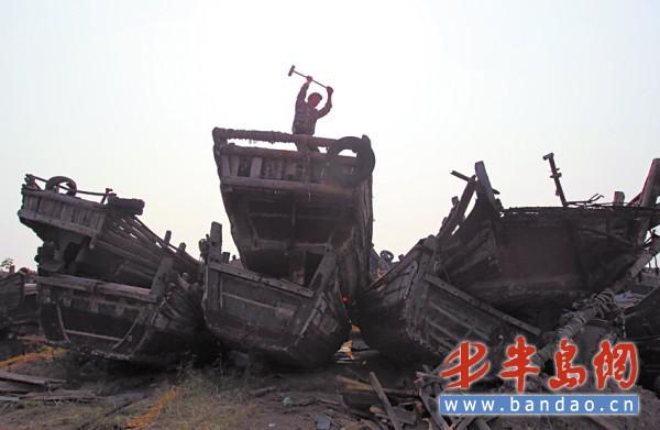 10月22日,在崂山区小麦岛废旧渔船堆积区,工作人员正在将废旧渔船