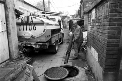 19日,法华寺东街,抽粪工普凤启将抽粪车上的管子插入井口开始工作。