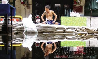 10月28日,曼谷湄南河边,当地一居民守在家门口前等着洪水的来临。每日涨潮的时候,这里的居民都会如临大敌。图/记者华剑