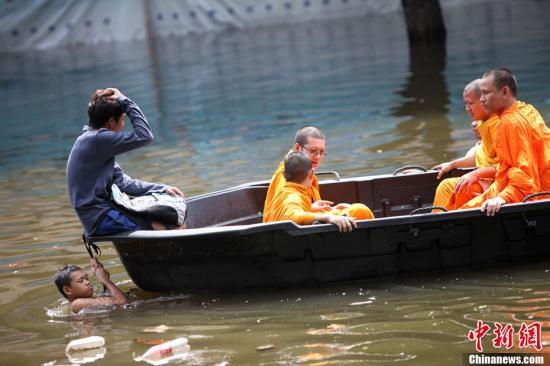 当地时间10月29日,泰国首都曼谷防洪警报仍未解除,防汛形势依然严峻。图为当天下午市区一防洪物资发放点,市民在排队领取沙袋、轻质砖块等防洪材料。中新社发 余显伦 摄