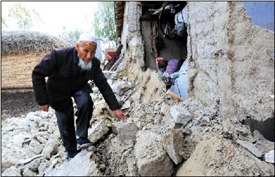 伊犁开买阿吾孜村村民保玉林在查看地震中受损的自家房屋.新华社发