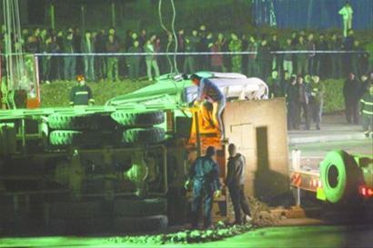 6时46分,在车祸现场,工作人员爬上侧翻的载重货车固定绳索,准