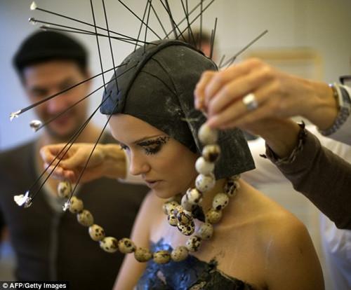 一名穿着巧克力裙的模特正在戴上鹌鹑蛋做的项链。