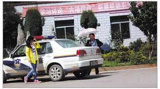 """照片上,打伞女子问黄衣女孩:""""你觉得这辆车比教练车如何?"""""""