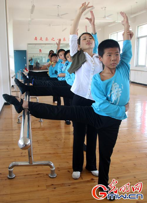 学生在舞蹈律动室里接受形体训练,动作还很到位.