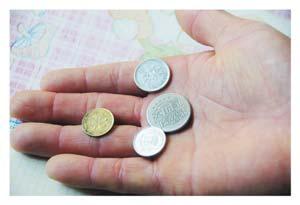施善 刘大军/馄饨店店主刘大军向记者展示老人给的游戏币、港币、日币和一...