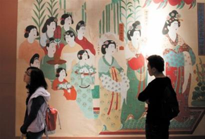 观众正在欣赏敦煌展的壁画艺术