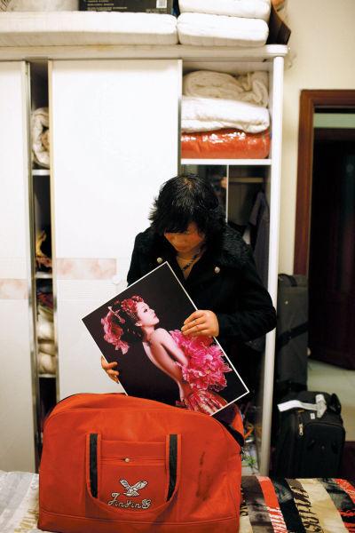 许丹继母整理着她生前的照片。