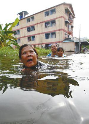 曼谷居民涉水经过洪水蔓延的街道。