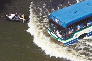 在曼谷洪水蔓延的街道上,乘坐小船的居民与一辆公共汽车相遇。