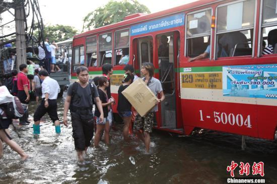 """11月7日,洪水继续向曼谷中心城区推进,有更多市民需要疏散,曼谷出动各种交通工具为市民代步。洪流中,公共汽车仍顽强地""""航行""""在既定的行车路线上。中新社发 余显伦 摄"""