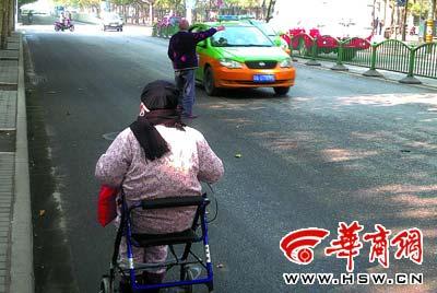 9日上午,七旬老太推着八旬老伴挡车,两个小时无一辆出租车停下来本报