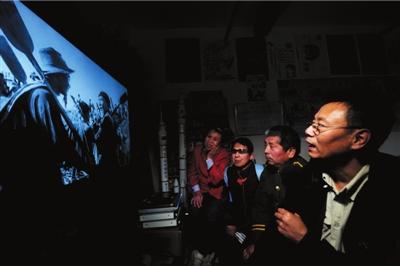 """王伟力(右)为盲人""""观众""""描述电影画面的细节。"""