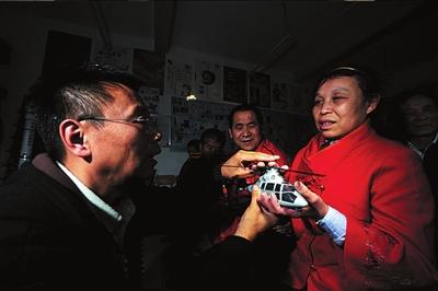 王伟力让盲人触摸他自备的模型以便更好地认知电影里的事物。