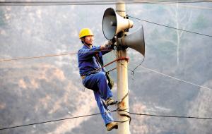 爬上电线杆,胡怀平维修村里的喇叭.图片