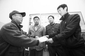 刘大爷庄重地将感谢信交到车队队长的手中。本报记者 李志华 摄