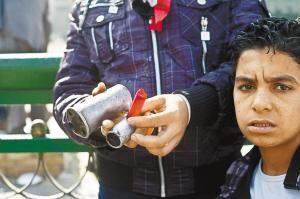 11月21日,在埃及首都开罗的解放广场,一名男子展示警察使用过的弹壳。新华社发