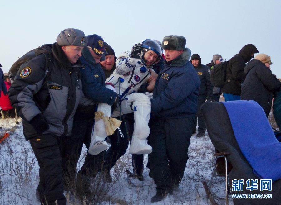 """11月22日,在哈萨克斯坦中部城市阿尔卡雷克以北的草原上,地面工作人员推着俄""""联盟TMA-02M""""载人飞船返回舱。"""