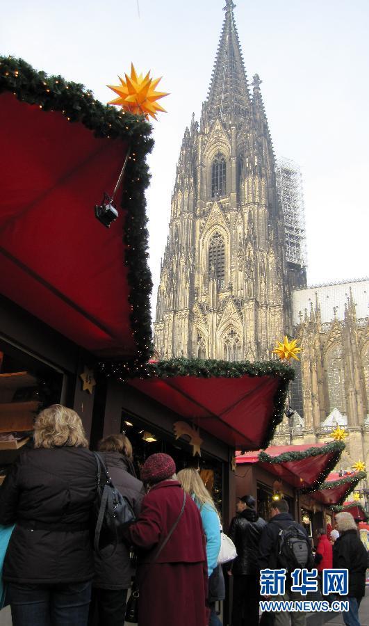 11月24日,人们在德国科隆大教堂下的圣诞市场游览购物