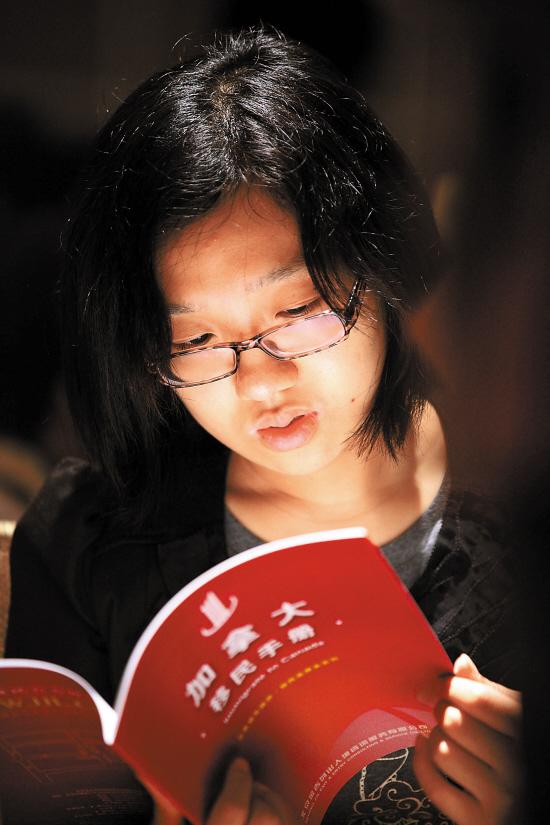 11月6日,市民在南京举行的国际教育展上浏览加拿大移民手册