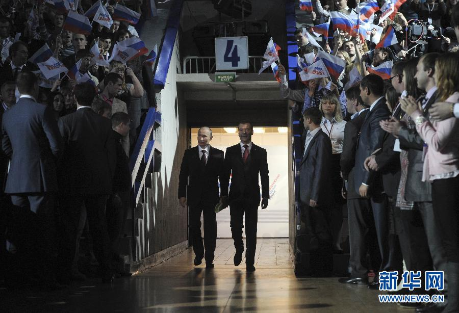 11月27日,在俄罗斯首都莫斯科,俄罗斯总统梅德韦杰夫(右)与总理普京在俄罗斯执政党统一俄罗斯党的代表会议上共同在台上发言。