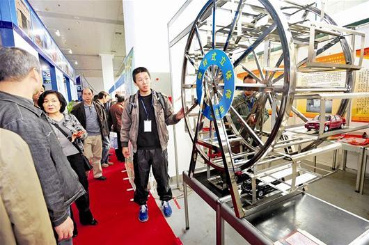 看展出的旋转式立体停车库模型 记者李辉摄 -市民热捧创业赶集会