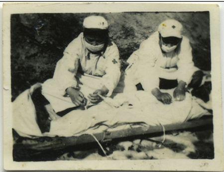 护士官义芝(左)和何成君在为黄继光遗体裹白布。(图片来源:环球网)