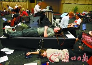 """12月11日,大会""""加时赛""""继续进行,两名疲惫不堪的与会者在会场外就地休息。"""