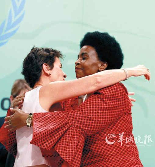 《联合国气候变化框架公约》执行秘书克里斯蒂安娜·菲格雷斯(左)与大会主席、南非国际关系与合作部长迈特·恩科阿纳-马沙巴内(右)在南非德班举行的联合国气候变化大会闭幕式上拥抱庆祝