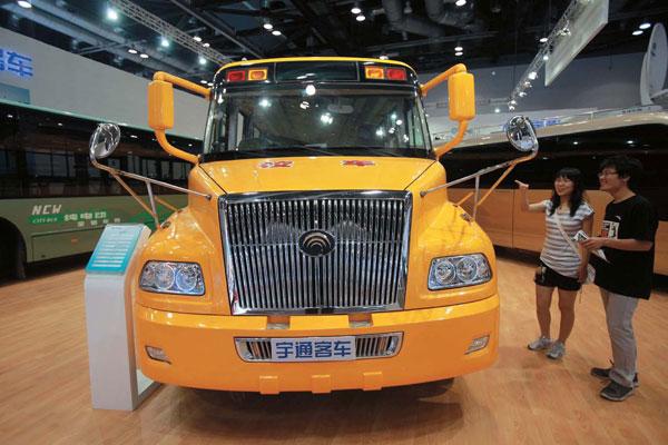 7月10日,一位观众在北京举行的第二届中国品牌汽车博览会上观看新型校车。CFP