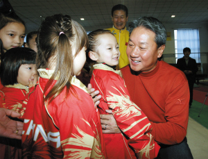 国家体操队总教练黄玉斌(右)与小朋友们在一起