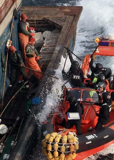 资料图:中国渔民使用渔刀阻止手持警棍的韩国海警登船