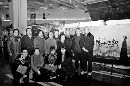 本报观影团部分读者在《金陵十三钗》海报前合影。