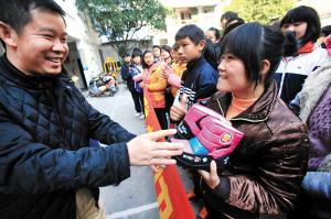 爱心人士给桂林聋哑学校学生发冬鞋。