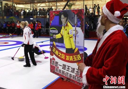 """12月16日,一位""""圣诞老人""""手捧玫瑰花出现伊春冰壶六国邀请赛现场。中新社记者 王中举 摄"""
